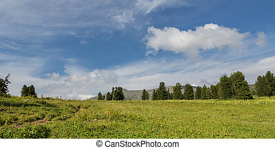 Beautiful blue sky with clouds over the top of Altai Mountains.
