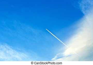 blue sky with condensation trail of an aircraft