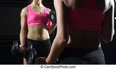 Beautiful body of a young woman with dumbbells in his hands.