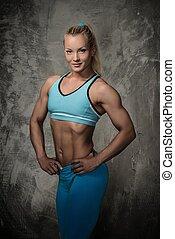 Beautiful bodybuilder woman on concrete background
