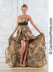 Beautiful bonde woman in leopard patterned long dress.