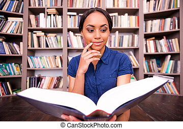 Beautiful bookworm. Thoughtful African female student...