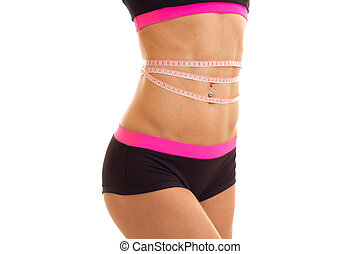 beautiful bouncy tummy and hips of a young girl in short shorts with belt at the waist close-up