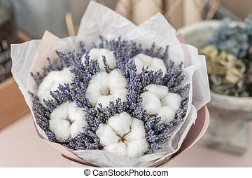 beautiful bouquet lavender and cotton, on table . dried flowers white and lilac color