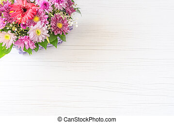 Beautiful bouquet of bright flowers in basket on white wooden background.