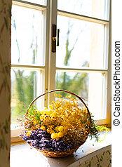 Beautiful bouquet of bright flowers in basket on window sill