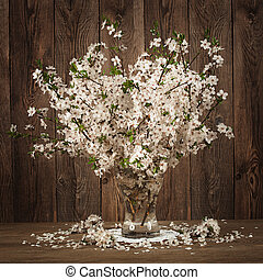 Beautiful bouquet of cherries in a vase on the old boards