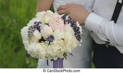 Beautiful bouquet of different colors in the hands of the bride in a white dress. Happy married couple with a wedding flowers.