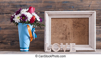 Beautiful bouquet of flower with photo frame on vintage wood background.