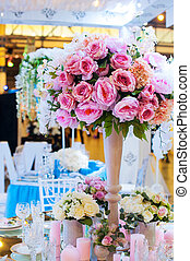 Beautiful bouquet of flowers at the wedding table in a restaurant decor.
