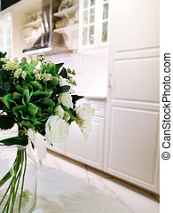 beautiful bouquet of flowers in a vase in a modern kitchen in bright colors.