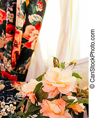 beautiful bouquet of flowers in a vase on the background of curtains and white tulle in the living room or bedroom.