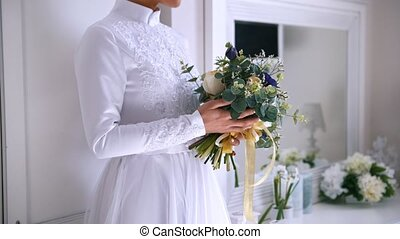Beautiful bouquet of flowers in hands of young bride dressed in white wedding dress
