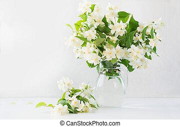 Beautiful bouquet of jasmine flowers in vase. Copy space.