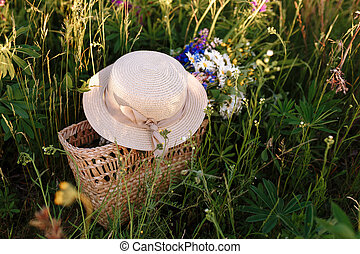 beautiful bouquet of lupines lies in a bag together with a straw hat on the grass in the field. Horizontal shot