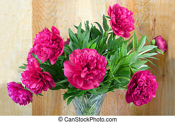 Beautiful bouquet of pink peonies on wooden background