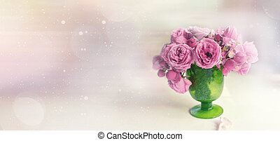 beautiful bouquet of pink peony roses stands on the table in a green glass vase against the background of the window. space for copying with bokeh. Banner