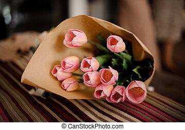 Beautiful bouquet of pretty pink tulips in kraft paper