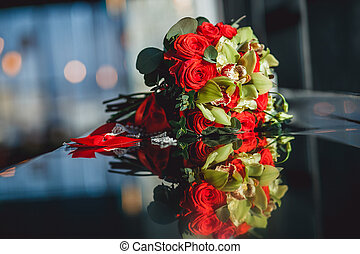 Beautiful bouquet of red roses arrangement for celebration and wedding. Closeup picture in sunlight with reflections on the table