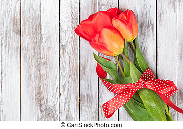 Beautiful bouquet of red tulips on wooden background. Space for text.