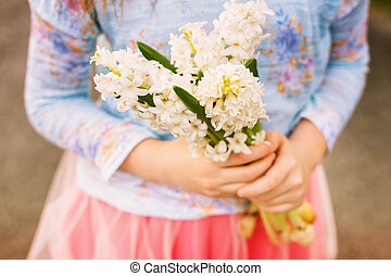 Beautiful bouquet of soft white hyacinth flowers in child's hands