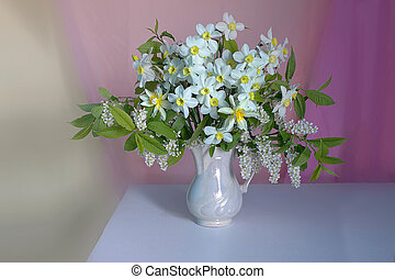 Beautiful bouquet of spring flowers in a vase isolated on a pink background.