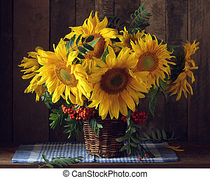 bouquet of sunflowers and branches of mountain ash