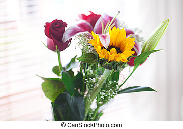 beautiful bouquet of sunflowers, lily and roses in a vase