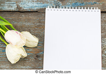 Beautiful bouquet of tulips for Mother's Day and blank paper with empty space for a text on wooden background