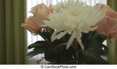 Beautiful bouquet of white chrysanthemum and pink roses in home interior.