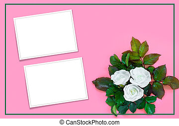 Beautiful bouquet of white roses and green foliage on pink paper background. Creative greeting card.