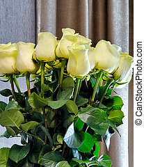 beautiful bouquet of white roses in a vase on the table