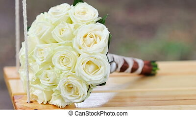 Beautiful bouquet of white roses lies on a swing in the park