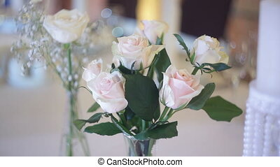 Beautiful bouquet of white roses on the wedding table in a restaurant