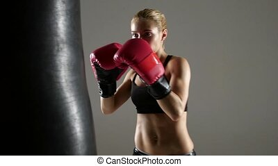 Beautiful boxer girl has an attempt on punching bag, dressed in black top visible to the waist, boxing gloves of red color on hands, close shot gray background, slow motion