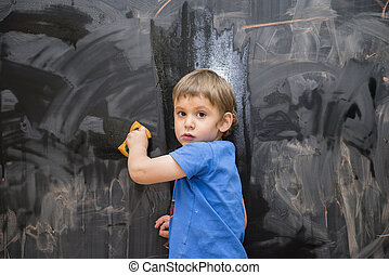 Beautiful boy drawing on a blackboard, young artist