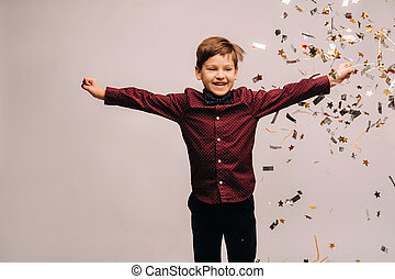 Beautiful boy jumping for joy and with confetti on a gray background