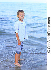 Beautiful boy stands on the seashore in summer. A child ...