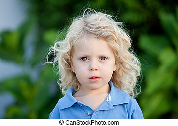 Beautiful boy three year old with long blond hair