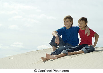 boys sitting on the sand