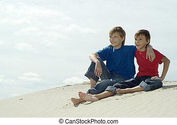 boys sitting on the sand