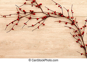 Beautiful branch with red berries on a wooden background