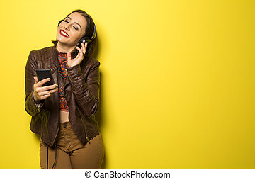 beautiful Brazilian girl enjoying music with the head phones in yellow background