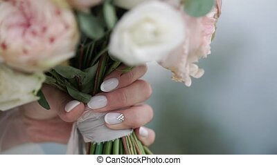 Beautiful bridal bouquet in hands of young bride dressed in white wedding dress. Close up of big bunch of fresh white and pink roses flowers in female hands. Anonymous bride holding flowers.