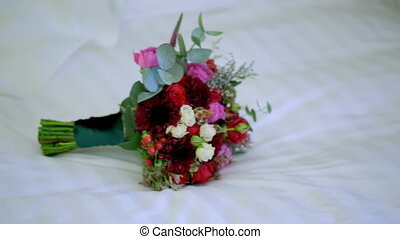 Beautiful Bridal bouquet lying on the bed.