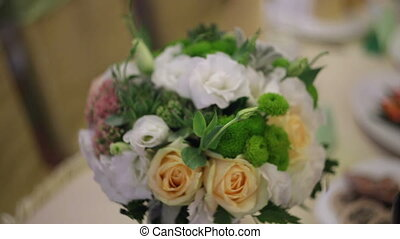 Beautiful bridal bouquet on the table bride and groom