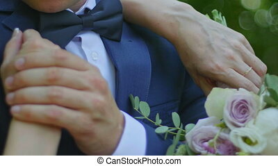 Beautiful bride and groom are kissing in a sunny park, close up