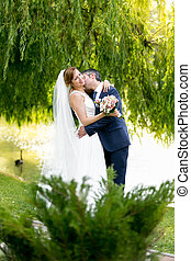 Beautiful bride and groom passionately kissing under tree