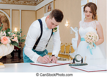 beautiful bride and groom signature in the registry office -...