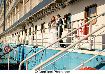 bride and groom standing on cruise ship deck at sunset
